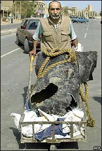 Man with part of a Saddam Hussein statue