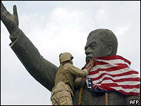 A US marine draping the Stars-and-Stripes on Saddam's statue