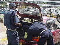 Security guards searching a car