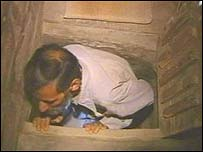 Jawad squeezes through the trapdoor into his hideout