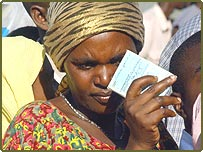 A voter holds her identity card as she lines up to cast her vote in the Kigali district of Nyiamirambo, 26 May 2003