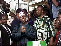 Olusegun Obasanjo (hands clasped) casts his vote in his home town, Abeokuta