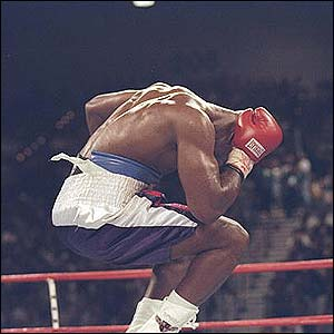 Evander Holyfield jumps in the air and holds his head in agony after Mike Tyson bit a piece off his right ear