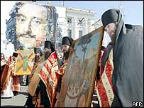 A religious procession walks in front of a portrait of Tsar Peter the Great during celebrations