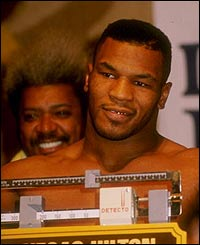 Mike Tyson listens to reporters during the weigh in for his fight against Trevor Berbick