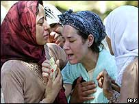 An Algerian woman is comforted by relatives at a funeral