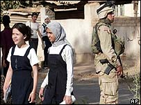 Iraqi girls head to school as US soldier stands guard in Baghdad, Iraq