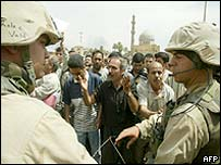 US marines guard a square in Baghdad where protesters shout anti-American slogans