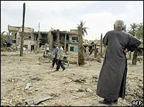 A Baghdad resident walks on a street littered with the rubble of destroyed buildings