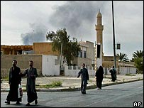 Residents walk down the nearly deserted streets as smoke billows in Tikrit, Iraq, Sunday, April 13, 2003
