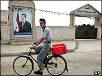 man cycles past mural of Saddam Hussein in Tikrit