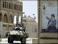 US Marines pass by a mural of Iraqi president Saddam Hussein as they move into Tikrit