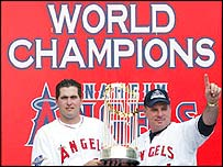 Baseman Troy Glaus and manager Mike Scioscia of the Anaheim Angels hold the world series trophy