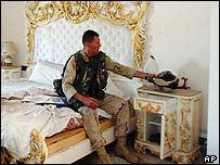 US marine places his helmet by a lavish bed in Uday's palace