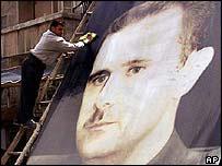Man polishes billboard of Syrian President Bashar al-Assad