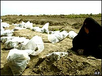 Iraqi woman sits beside the bodies of those found in mass grave at Mahawil