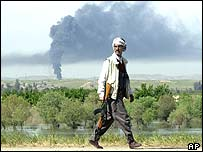 Peshmerga fighter on patrol as smoke rises from a burning oil field near Mosul, northern Iraq