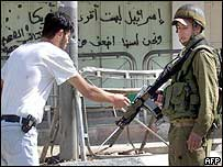 A Palestinian shows his ID to an Israeli soldier in Hebron