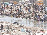 Iraqi people take water from a polluted area for household needs in Basra