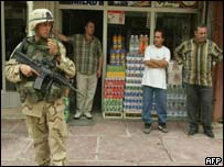 A US soldier stands guard in front of a store during a search for automatic weapons