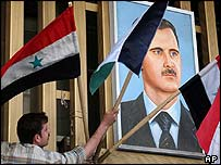 Syrian worker hangs flags next to portrait of President Bashar al-Assad