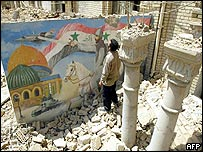 Iraqi man stands next to a picture depicting war in the rubble of the defence ministry