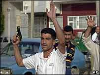 An Iraqi policeman shoots into the air to disperse a crowd