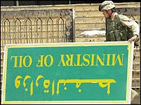 US soldier walks past an overturned sign at the Iraqi Oil Ministry