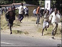 Zimbabweans run from riot police and tear gas