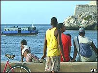 Cubans watch a hijacked ferry being towed back into port