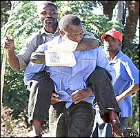 Leonard Chigwagwi is carried by a colleague after being shot in Highfield