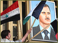 A worker hangs Syrian flags, with a Baath Party flag at centre, next to a portrait of Syrian President Bashar Assad on a building in Damascus.