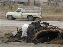 Iraqis checked wrecked tank in outskirts of Baghdad
