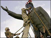 US soldiers put a Stars and Stripes over a Saddam statue in Baghdad