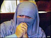 A female legislator from the ruling religious parties alliance give thanks with tears in their eyes as Islamic law is approved