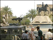 US soldiers stand guard in front of a statue of toppled Iraqi President Saddam Hussein in Tikrit