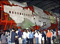 Journalists look at a Boeing 747-200 reconstruction from China Airlines wreckage 03 June 2003, in Taoyuan air force base.