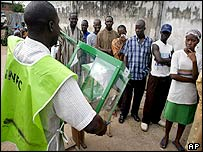 Election official shows voters empty ballot box before voting starts in Abeokuta