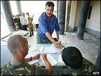 Iraqi man applying to be police officer shakes hands with British soldiers interviewing for posts