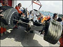 Jos Verstappen's Minardi is lifted back to the pits