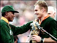Francois Pienaar (right) receives the trophy from then South African President Nelson Mandela