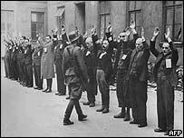 Un soldado nazi inspecciona a trabajadores judíos en el ghetto de Varsovia