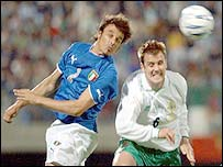 Italy's Massimo Oddo jumps for a header with Danny Griffin of Northern Ireland