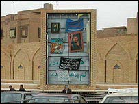 Frame for portrait of Saddam Hussein covered in Shia pictures and banners
