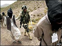 US soldiers of the 82nd Airborne lead Afghan prisoners suspected of being Taleban or al-Qaeda forces, 2 June 2003