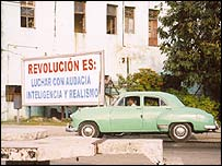 Old car passes revolutionary slogan in Havana