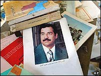 A picture of Saddam Hussein in the mess left behind in a looted Iraqi school