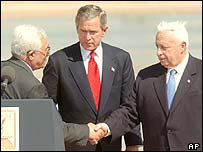 George Bush watches as Abu Mazen (left) shakes hands with Ariel Sharon