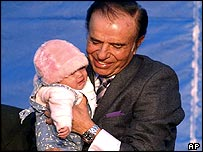Carlos Menem whose wife is expecting a child holds a baby at a campaign rally