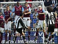 Solano curls the ball round the Aston Villa wall